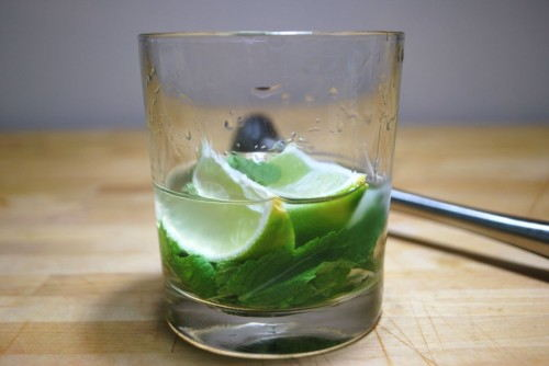 Muddle the limes, mint and rum