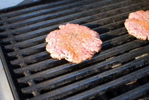 Place the burger directly over the heat and season lightly with seasoning salt